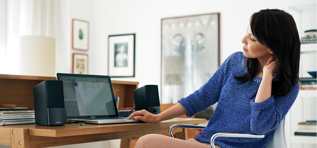 Woman relaxes listening to the Bose Companion 2 Series III multimedia speaker system